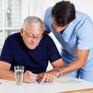 male-nurse-helping-senior-man-in-solving-puzzle